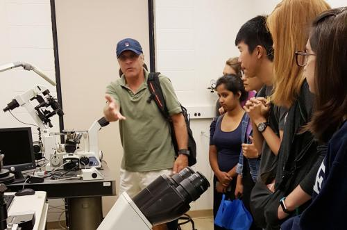 Prof. Paul Forscher giving a tour to students on various microscopy setups.