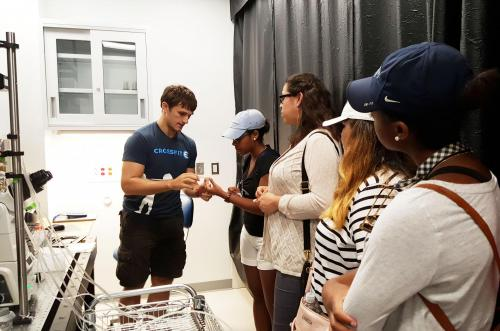 A MEMS/PEB student in the Howard lab showing Connecticut College students a microfluidics chamber..